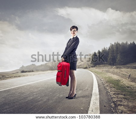 Smiling young businesswoman holding a suitcase on a country road - stock photo