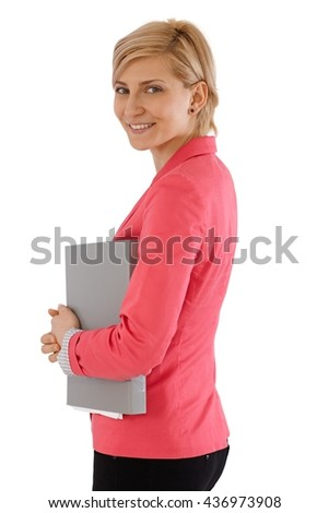 Smiling young businesswoman holding folder, looking at camera. - stock photo