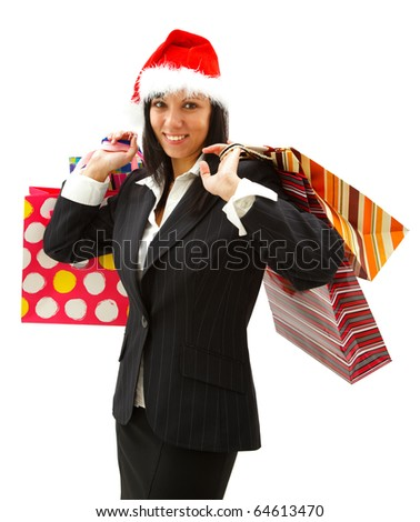 Smiling young businesswoman in santa hat with shopping bags