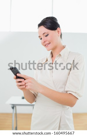 Smiling young businesswoman looking at cellphone in a bright office
