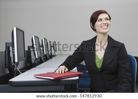 Smiling young businesswoman looking up at desk - stock photo