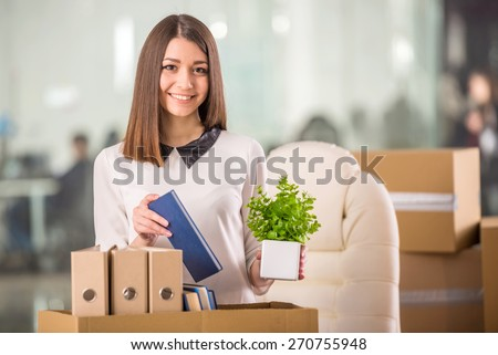 Smiling young businesswoman packing boxes and looking on camera in office. - stock photo