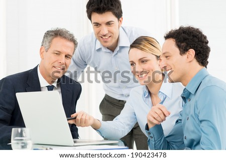 Smiling Young Businesswoman Showing Presentation On Laptop To Her Colleague - stock photo