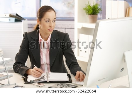 Smiling young businesswoman sitting in bright office, working with computer at desk, taking notes.