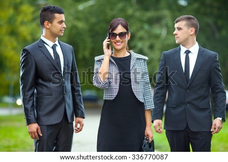 Smiling young businesswoman talking on the phone while walking on the street with two businessmen