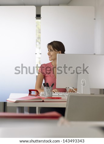 Smiling young businesswoman using computer at office desk