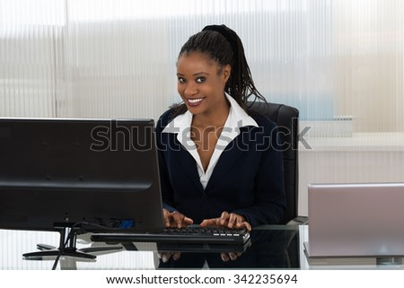 Smiling Young Businesswoman Using Computer At Office Desk - stock photo