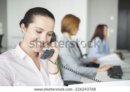 Smiling young businesswoman using landline telephone with colleagues in background at office - stock photo