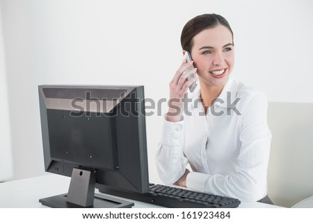 Smiling young businesswoman using mobile phone in front of computer in office