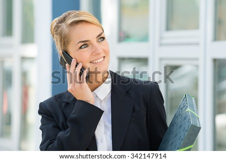 Smiling young businesswoman using mobile phone while looking away