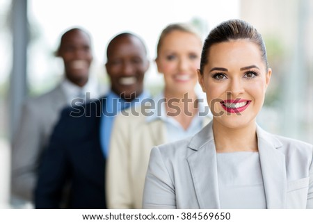 smiling young businesswoman with colleagues standing in a row