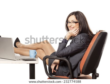 Smiling young businesswoman with her legs on the table - stock photo
