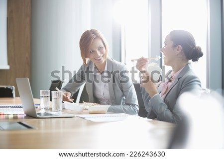 Smiling young businesswomen having lunch at table in office - stock photo