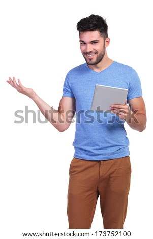 smiling young casual man holding a tablet pad is inviting you on white background - stock photo