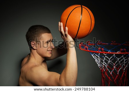 Smiling young Caucasian basketball athlete throwing the ball into the basket - stock photo