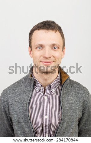 Smiling young Caucasian man in casual clothing, studio portrait over white background - stock photo