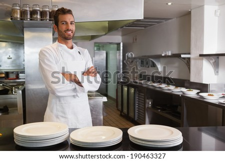 Smiling young chef standing with arms crossed behind counter in a commercial kitchen