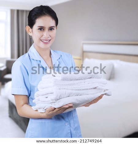 Smiling young cleaning lady holding towels shooting at hotel room - stock photo