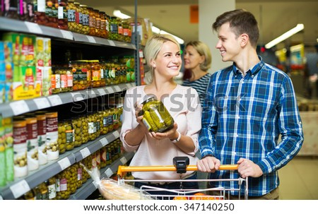 Smiling young clients buying tinned food at grocery shop - stock photo