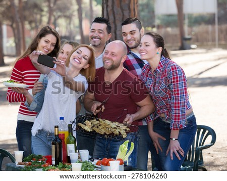 Smiling young colleagues making mutual photo at summer grill party - stock photo