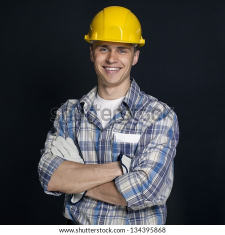 smiling young construction worker on a black background - stock photo