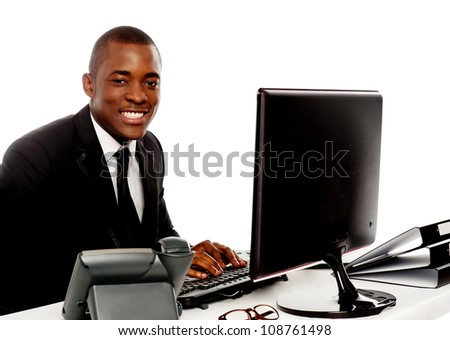 Smiling young corporate man using computer looking at camera - stock photo