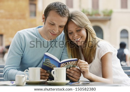 Smiling young couple at outdoor cafe looking at guidebook of Rome - stock photo