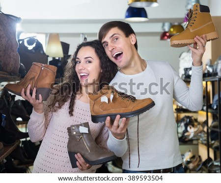 Smiling young couple buying winter shoes in a shoe shop - stock photo