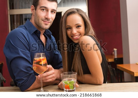 Smiling young couple drinking a cocktail in a bar. - stock photo