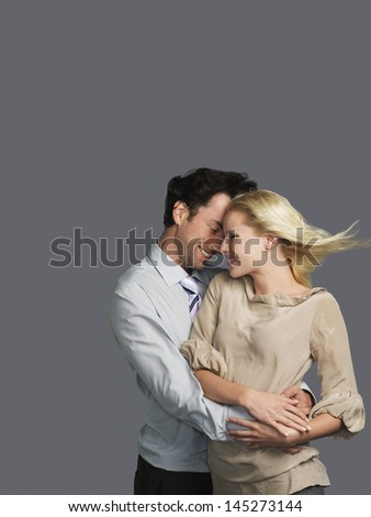 Smiling young couple embracing against gray background - stock photo