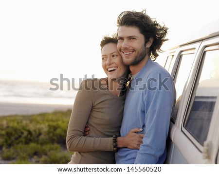Smiling young couple embracing by campervan on beach - stock photo