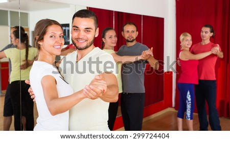 Smiling young couple enjoying of partner dance in dance class - stock photo