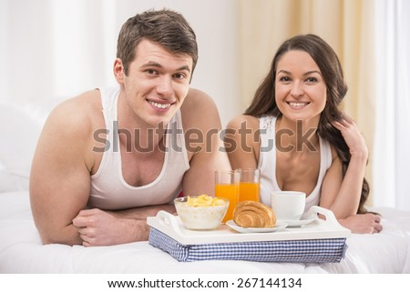 Smiling young couple having breakfast in bed. looking at camera.