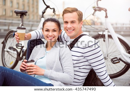 Smiling young couple having coffee - stock photo