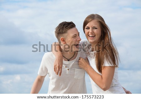 smiling young couple having fun in summer on the beach