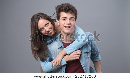 Smiling young couple having fun together and piggybacking - stock photo