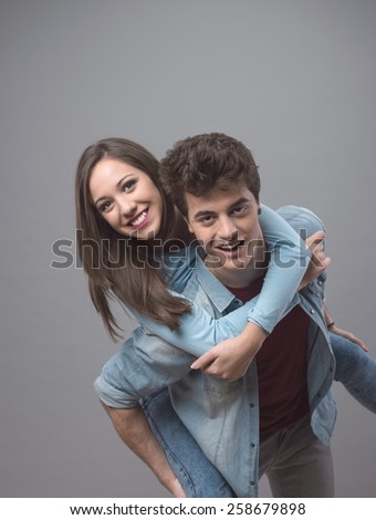 Smiling young couple having fun together and piggybacking