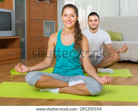Smiling young couple having yoga class at home. Focus on girl - stock photo