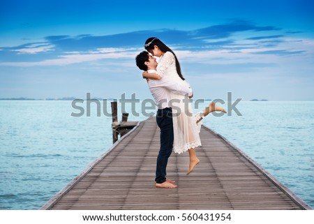 Smiling young couple hug while standing on wooden bridge near the sea