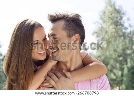 Smiling young couple looking at each other in park - stock photo