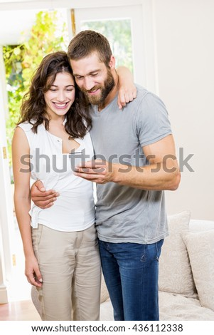 Smiling young couple looking at mobile phone in living room at home - stock photo