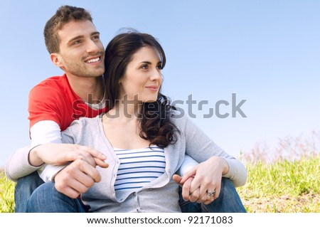 Smiling young couple looking together at their future - stock photo