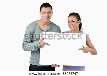 Smiling young couple pointing at sign they are holding against a white background