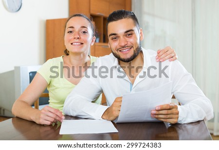 Smiling young couple signing financial documents at the table at home