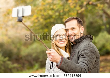 Smiling young couple taking selfies on an autumns day - stock photo