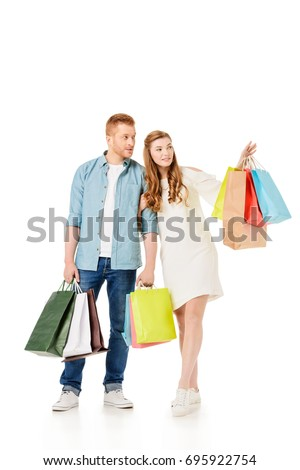 smiling young couple with colorful paper bags pointing away isolated on white