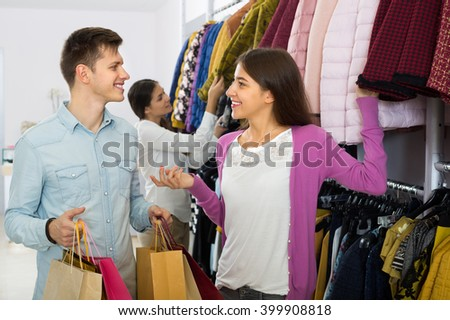 Smiling young couple with shopping bags choosing new apparel at the shop
