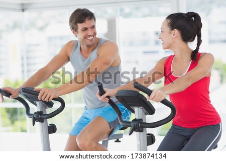 Smiling young couple working out at class in a bright gym - stock photo