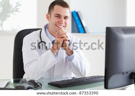 Smiling young doctor sitting at his desk - stock photo