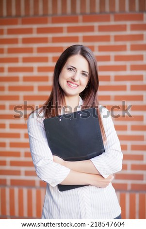 Smiling young elegant businesswoman with clipboard standing in a bright office  - stock photo